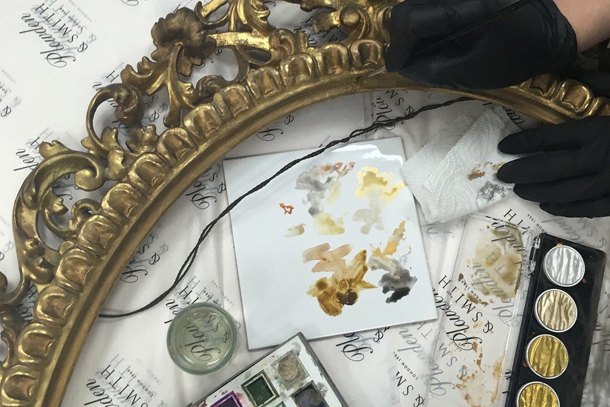 professional gilder gilding an antique gilt picture frame at the Plowden & Smith studio