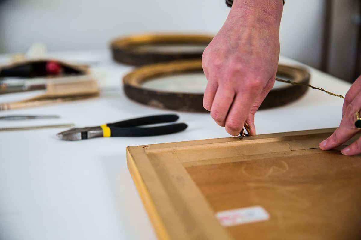 painting restorer conservation framing a painting
